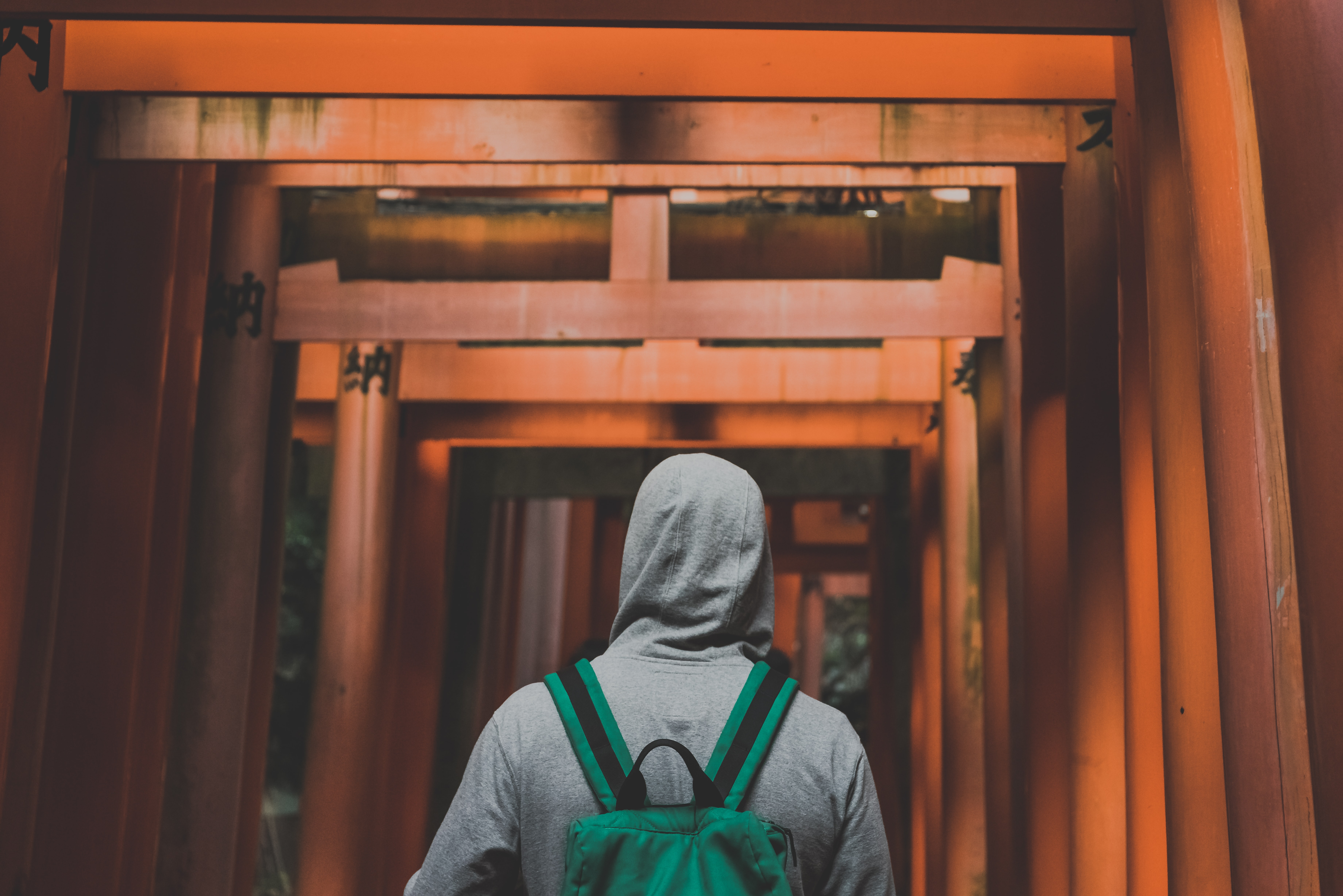 man with gray hoodie walking on wooden arcs