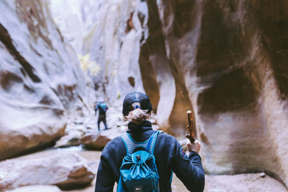two people hiking in the middle of huge rock formations