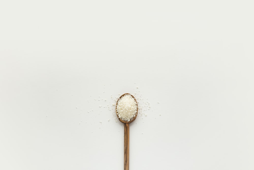 white powder on brown wooden spoon