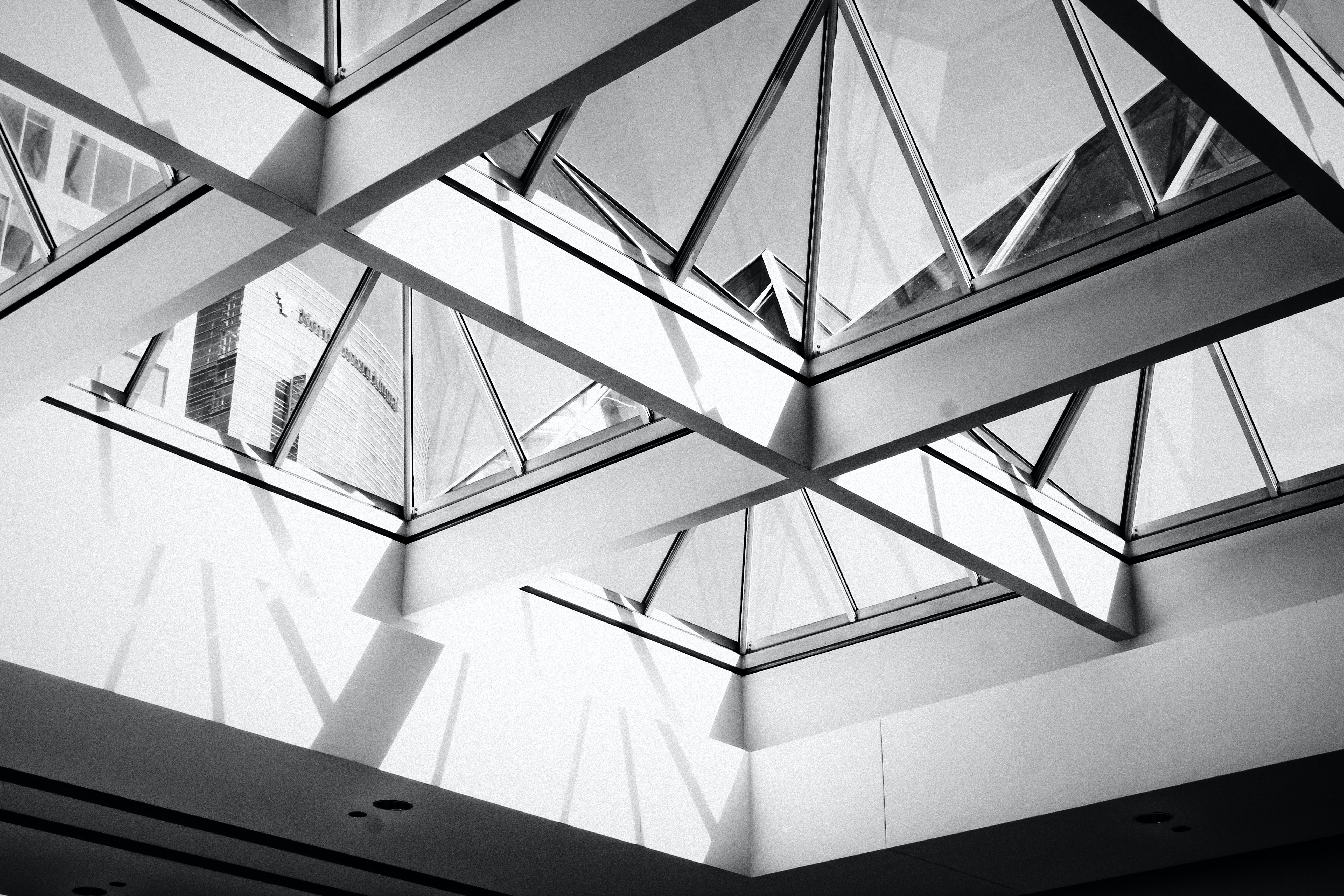 low angle photography of white framed glass roof