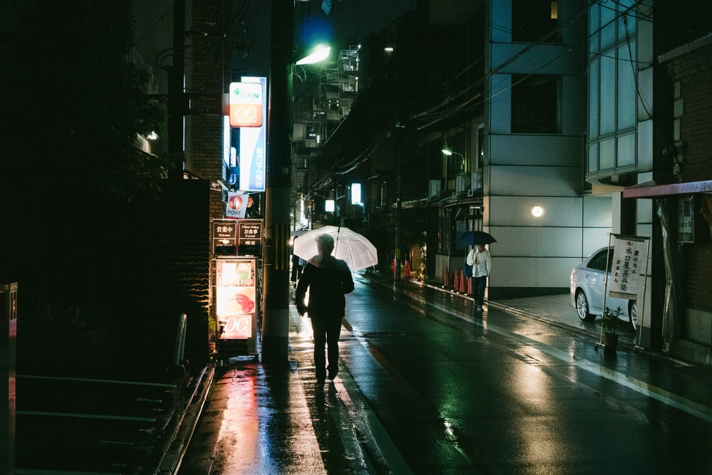 person holding umbrella near building at night time