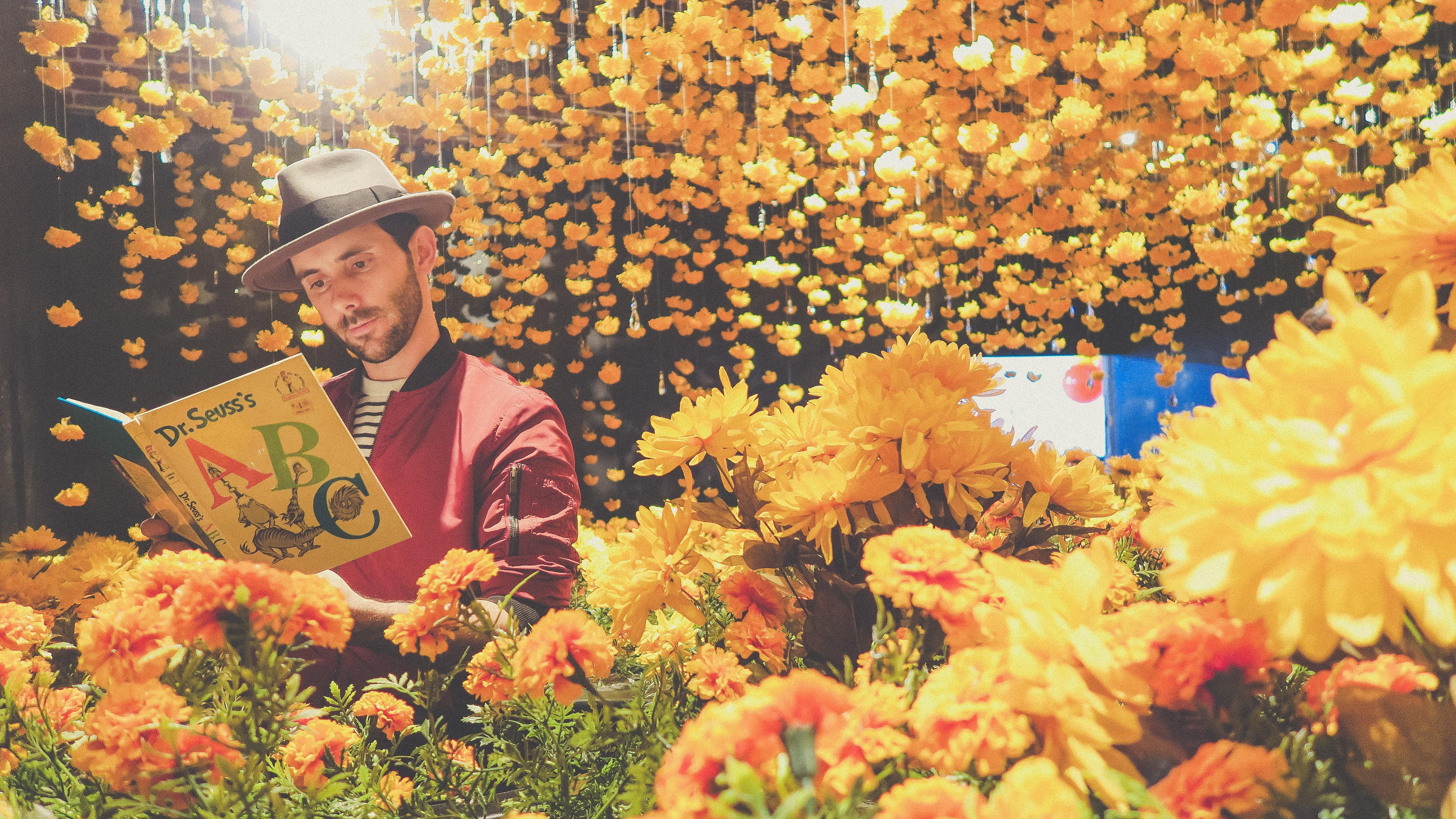 man reading book near yellow flowers