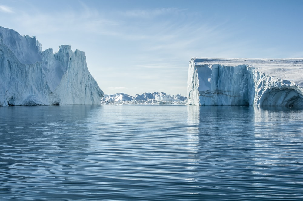 icebergs on body of water under blue and white sky at daytime