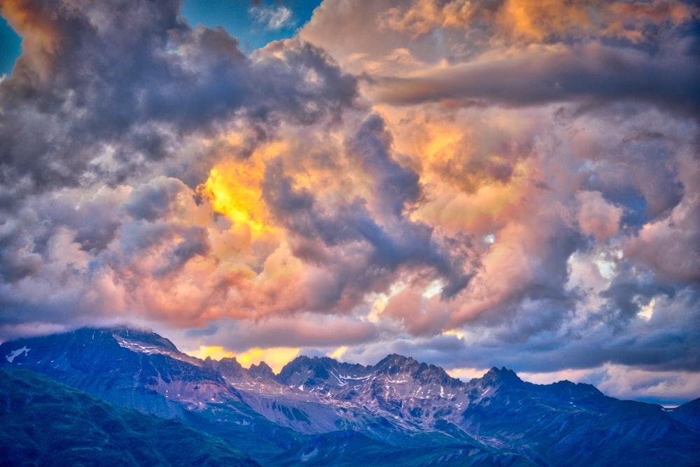 photo of mountain range under golden sky
