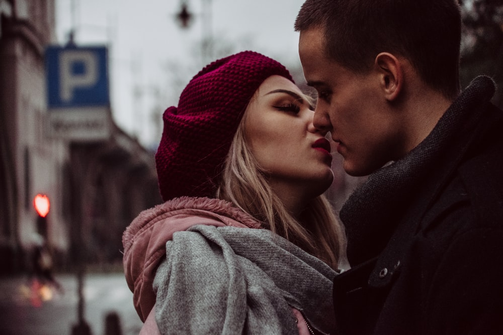 man and woman standing while kissing beside street signage