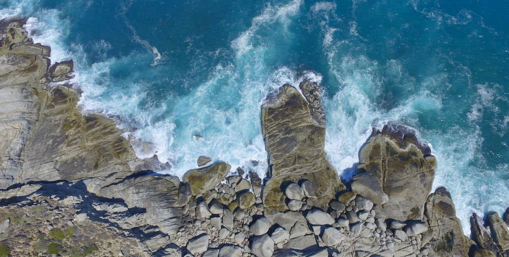 aerial photo of body of water near rock formation