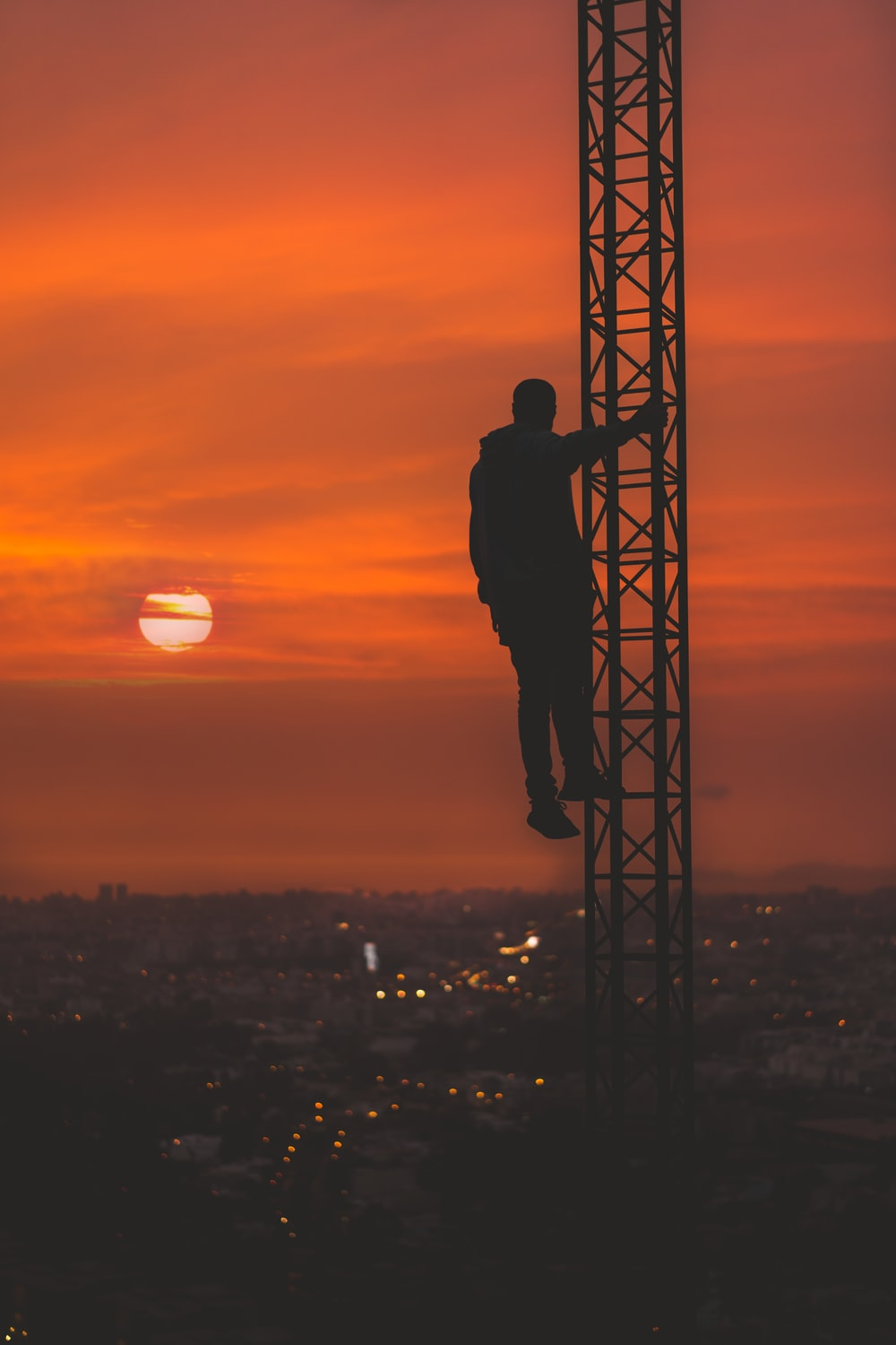 silhouette of man climbing tower during sunset