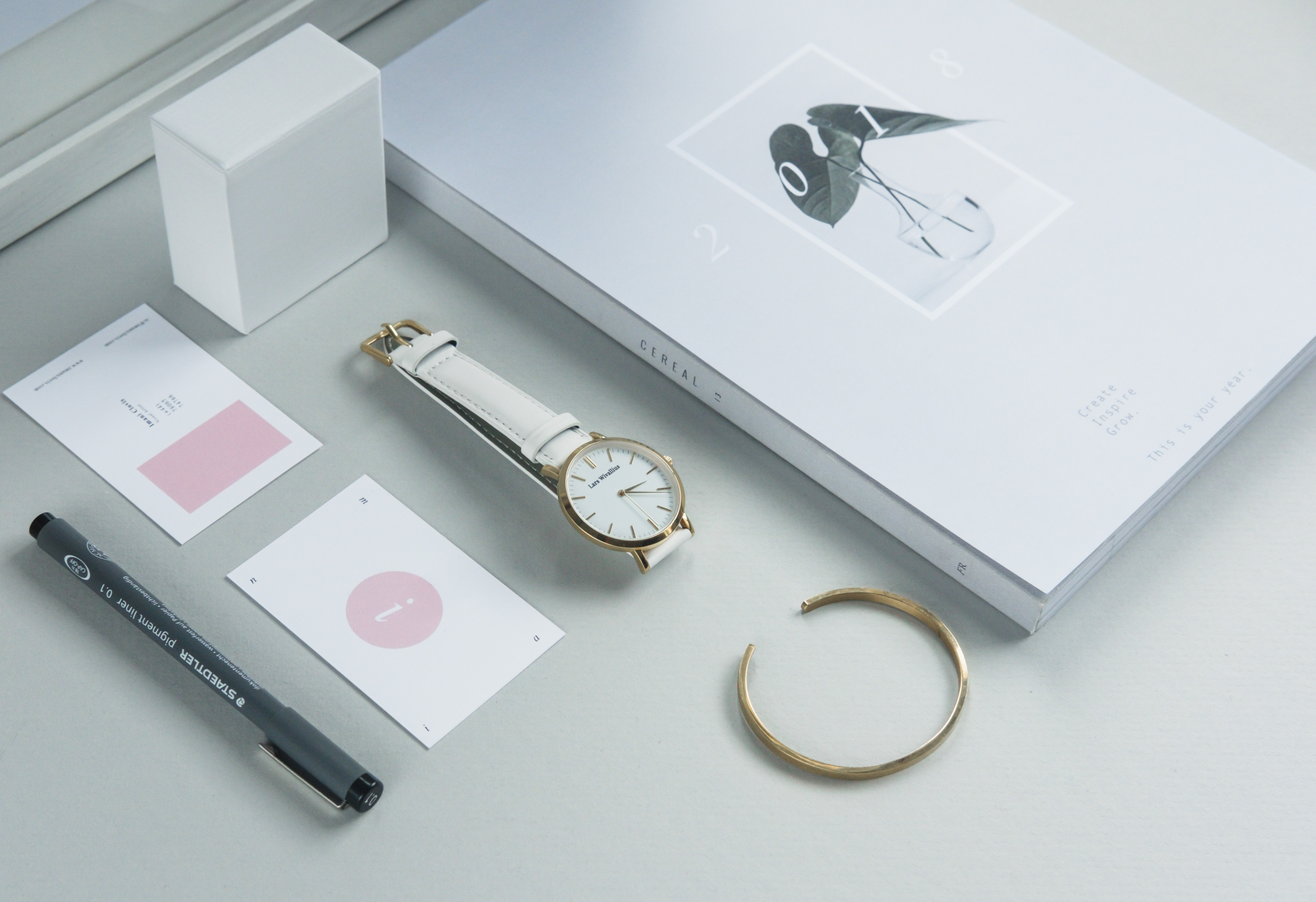 round gold-colored analog watch with white band