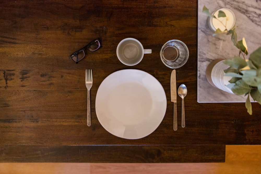 white ceramic plate on brown wooden table