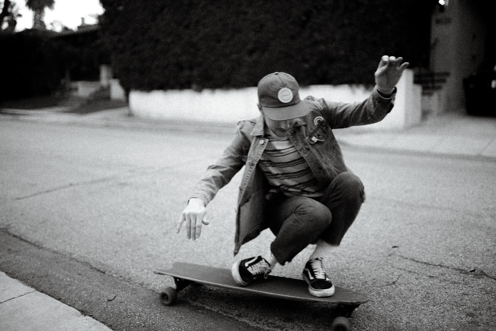 grayscale photography of person riding on longboard