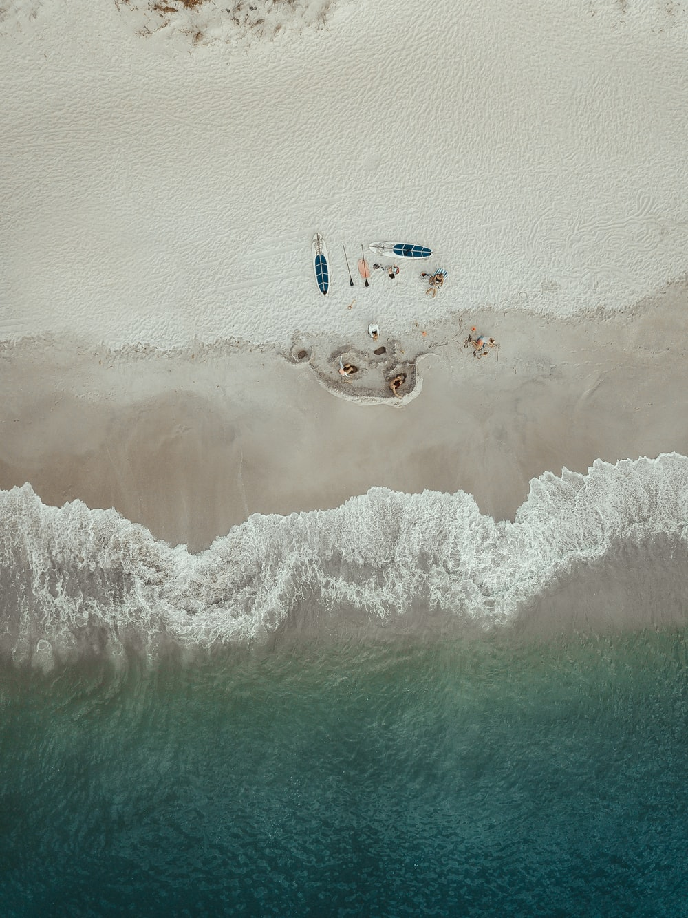 aerial photo of people lying on seashore near kayaks during daytime