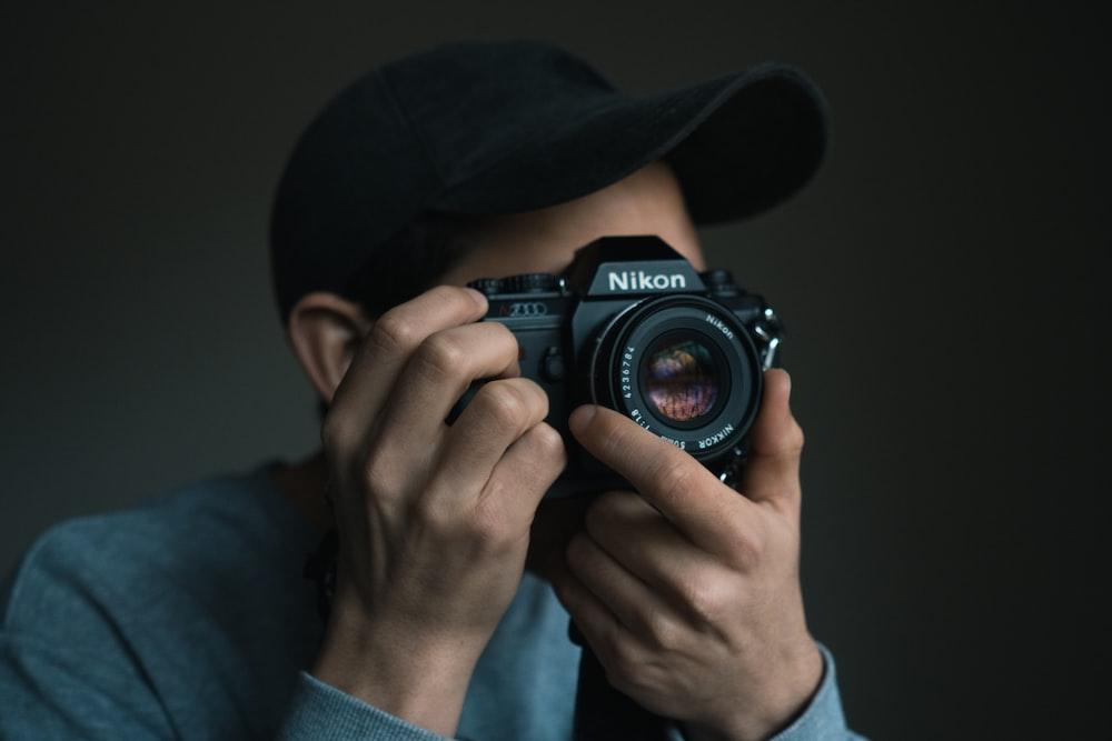 person using Nikon DSLR camera