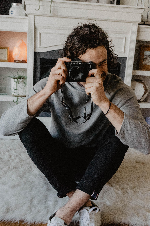 man holding DSLR camera sitting on white fur rug