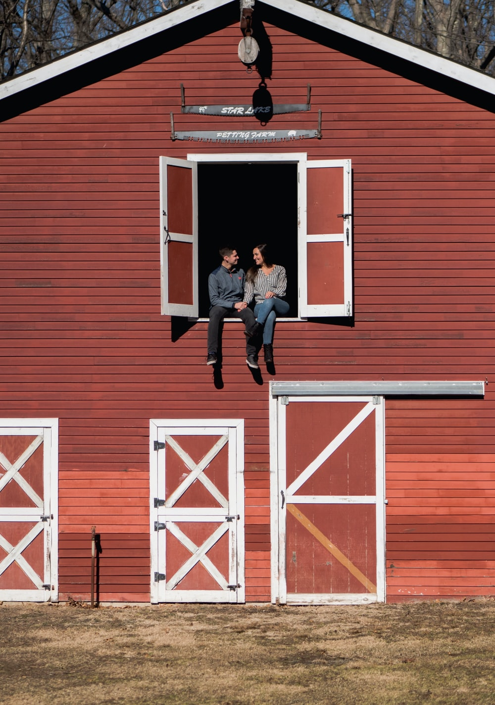 man and woman sitting in stable window