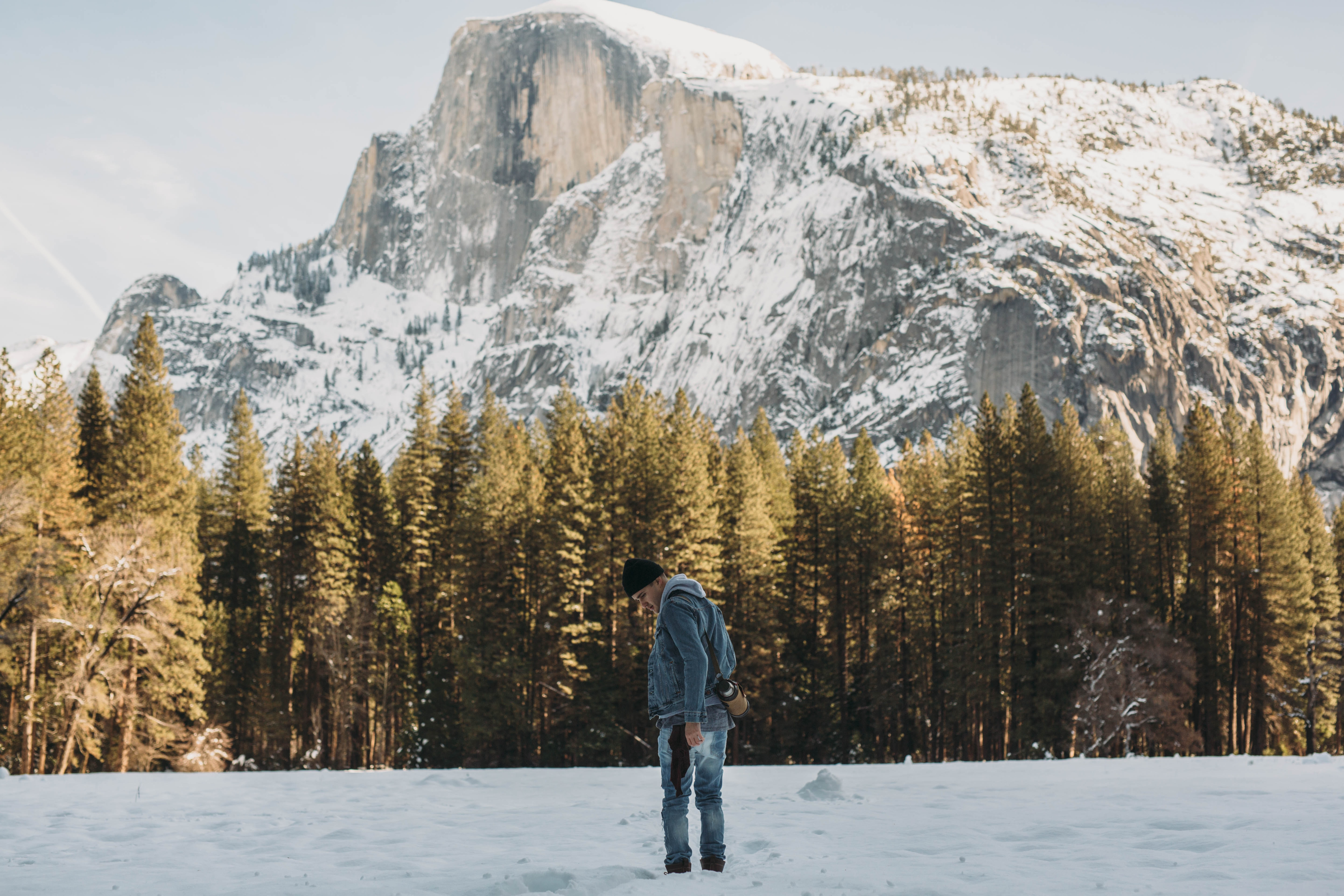 man standing on snow field near trees and mountain during day