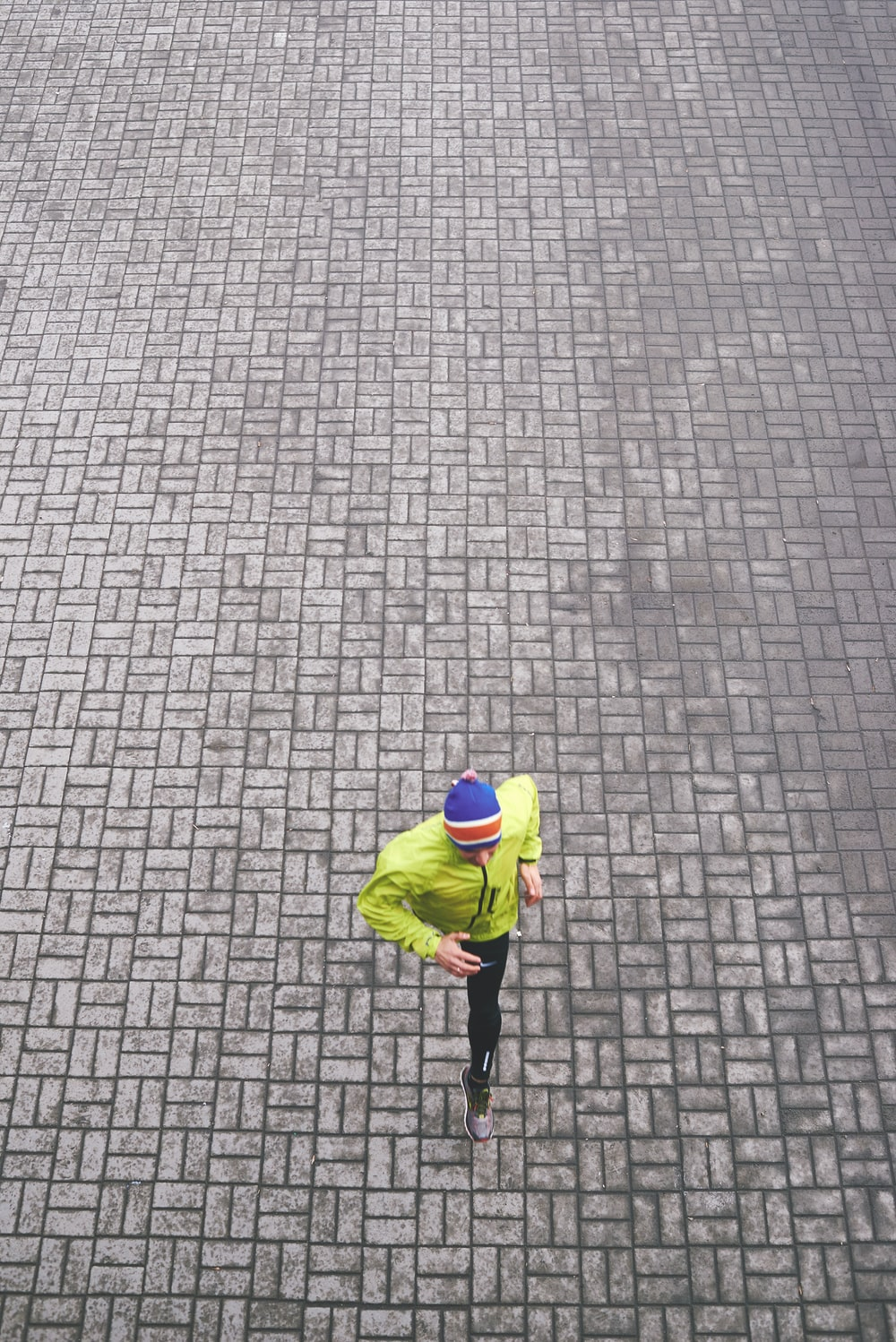person in green track jacket running