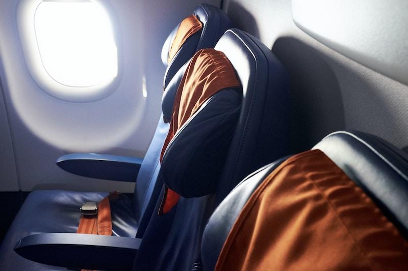 black leather airplane seat beside window
