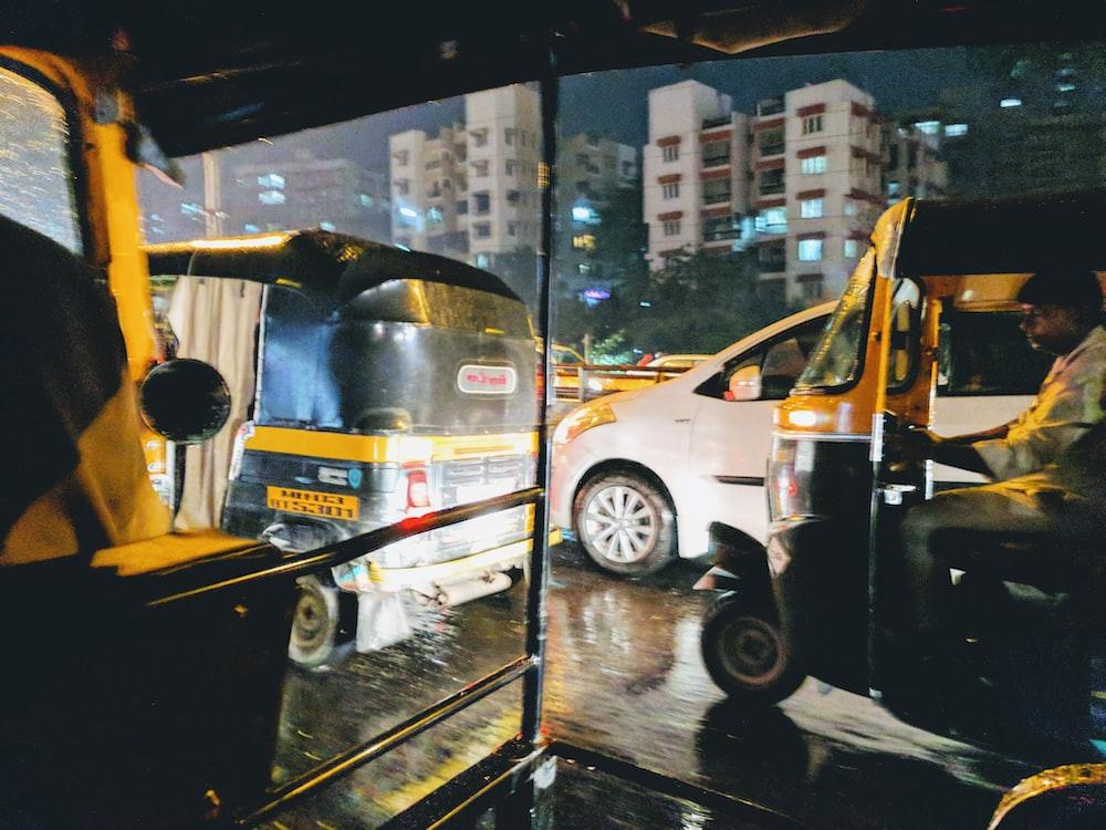 man riding on yellow and black auto rickshaw during daytime