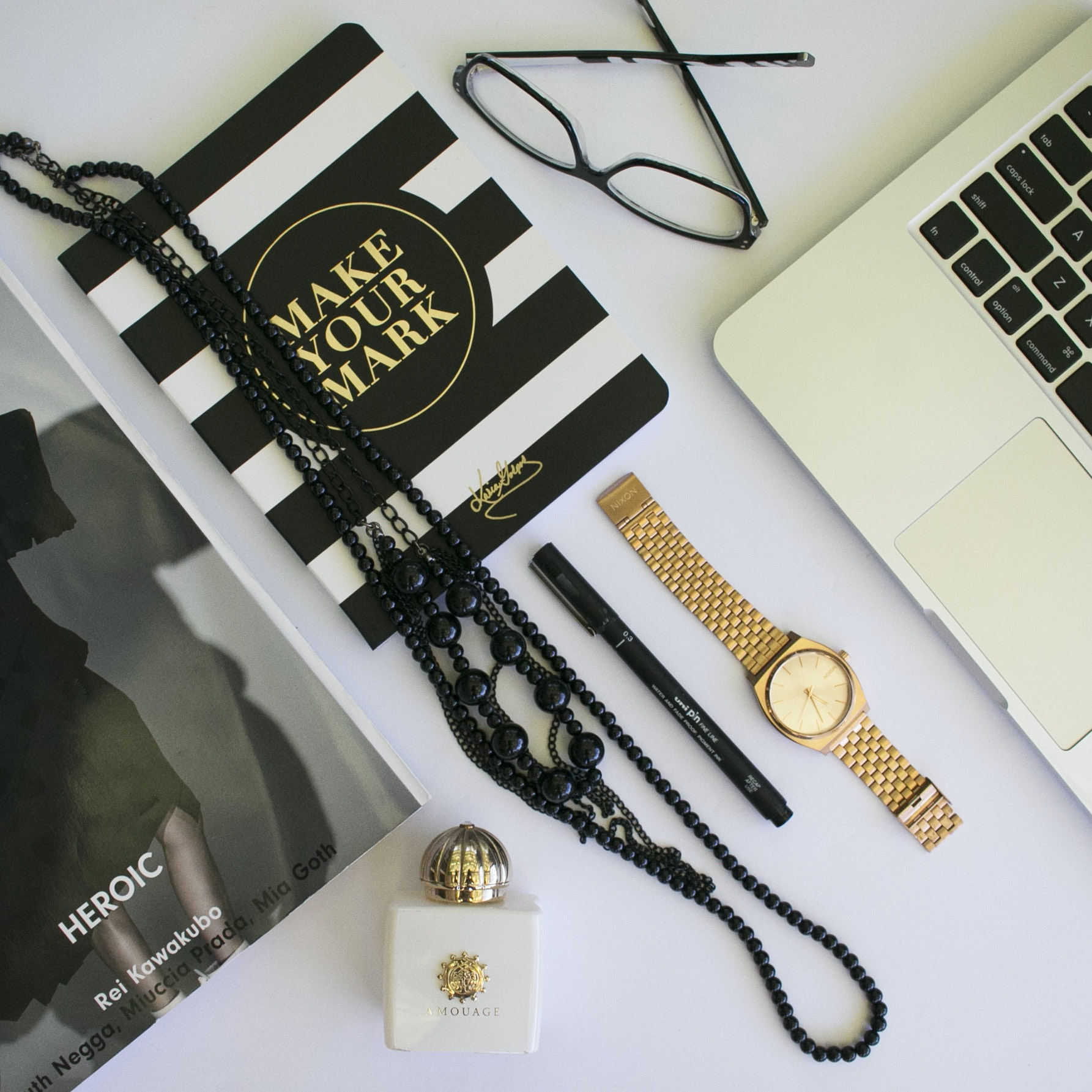 clear eyeglasses with black frames; beaded black necklaces; black pen; round gold-colored analog watch with link bracelet in flat lay photography