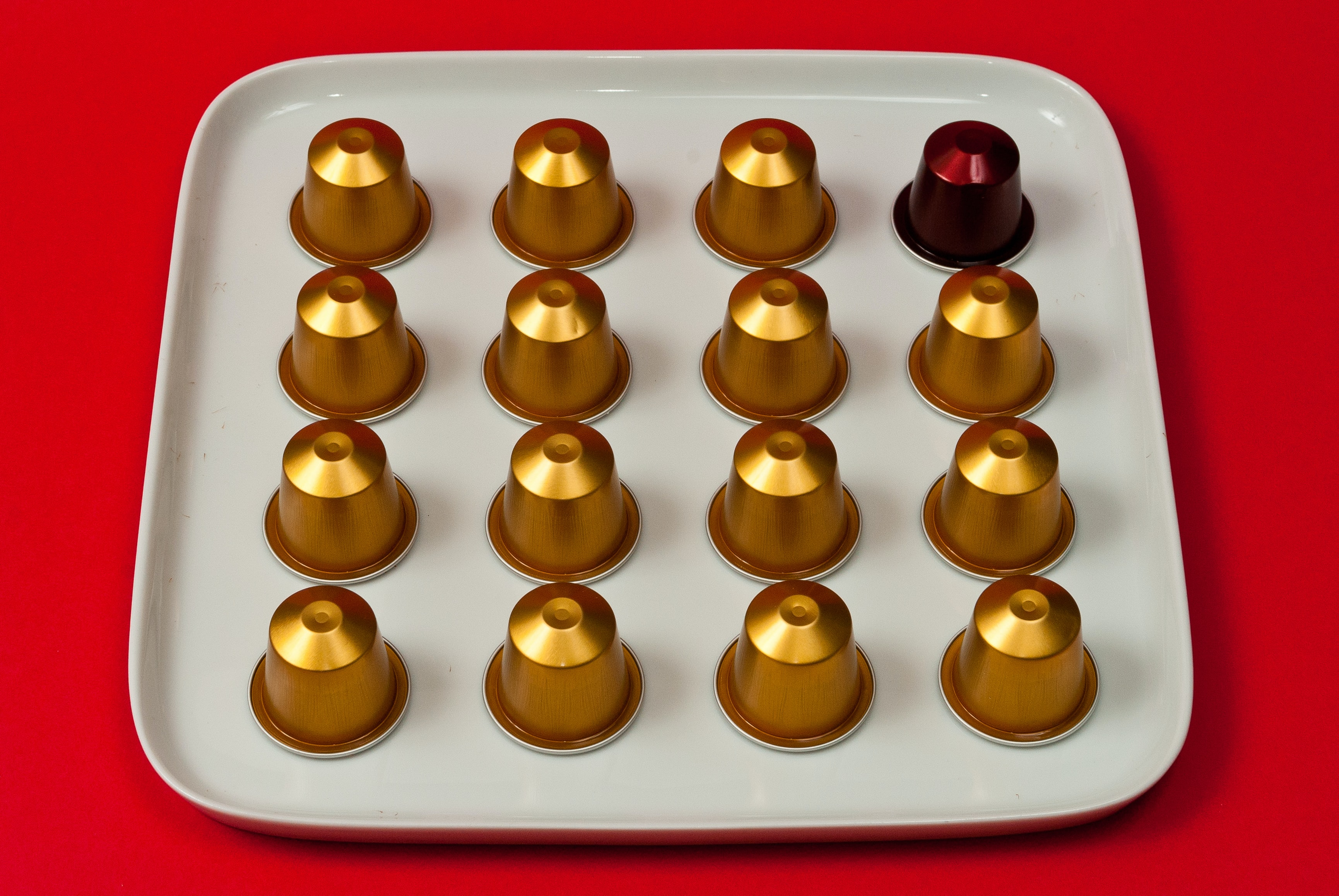 round brass-colored and maroon dome molds on white platter