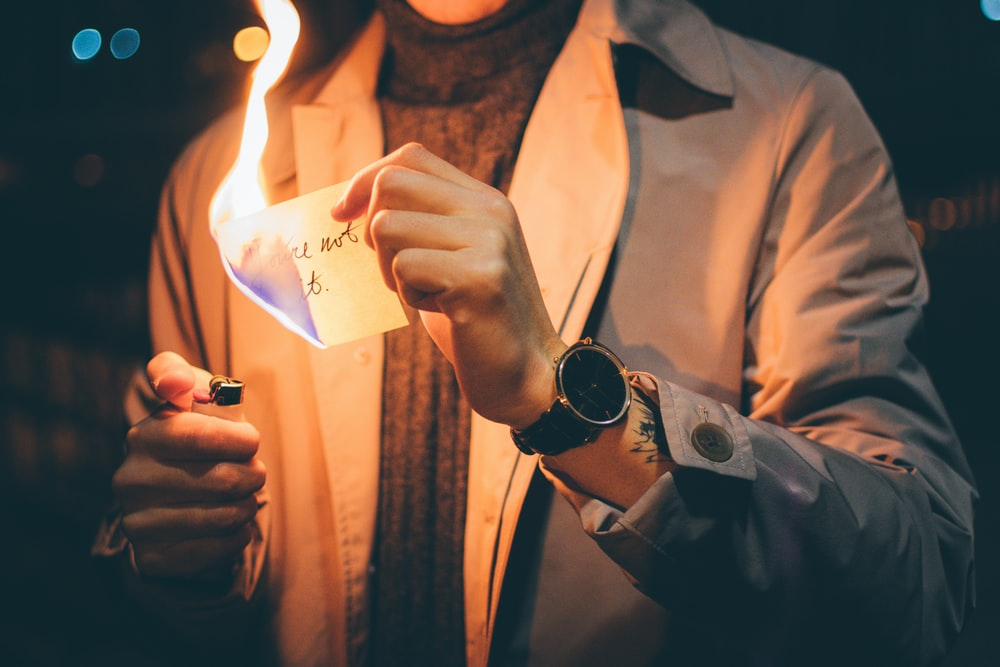 low light photography of person holding paper with flame