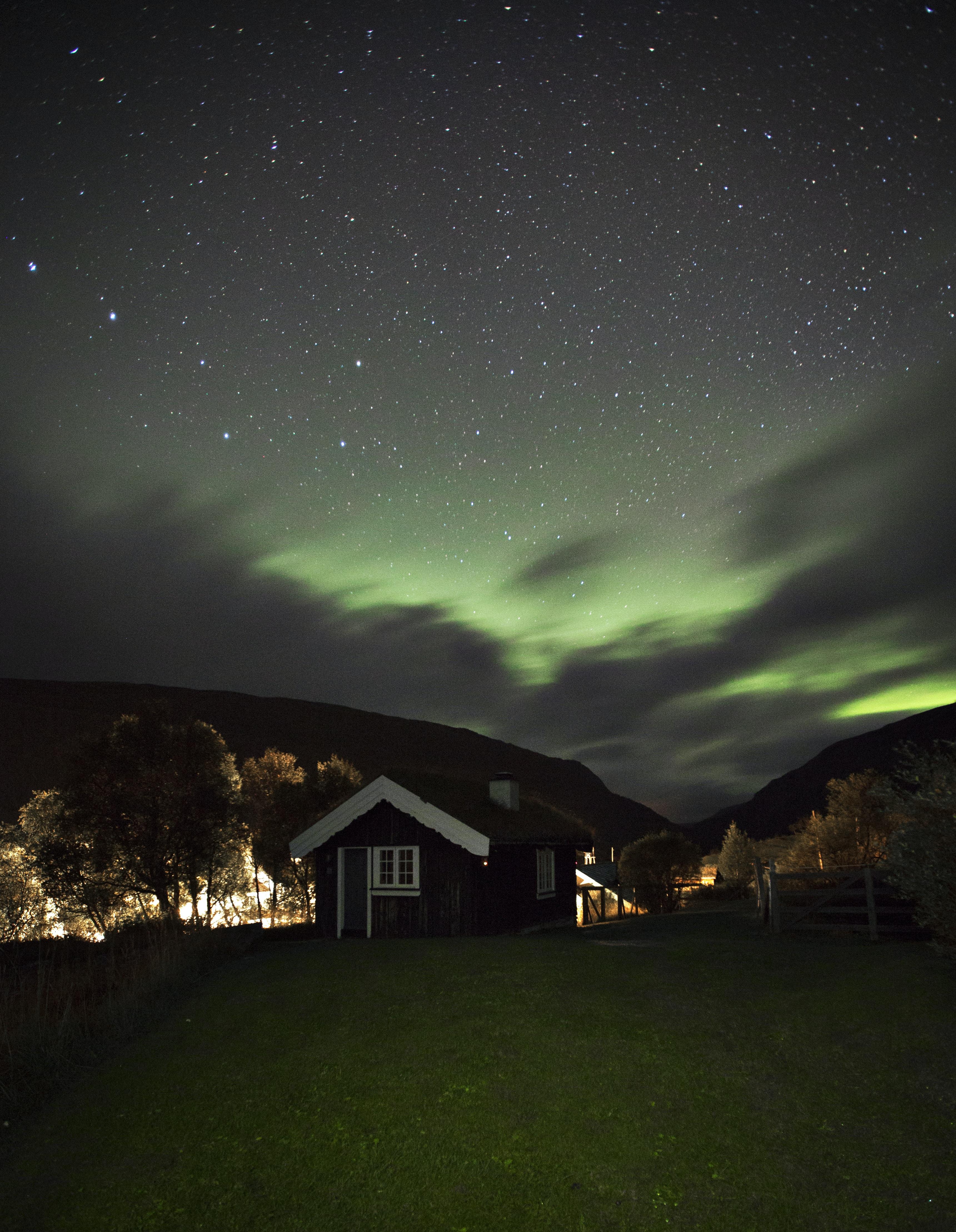 shed under green aurora sky