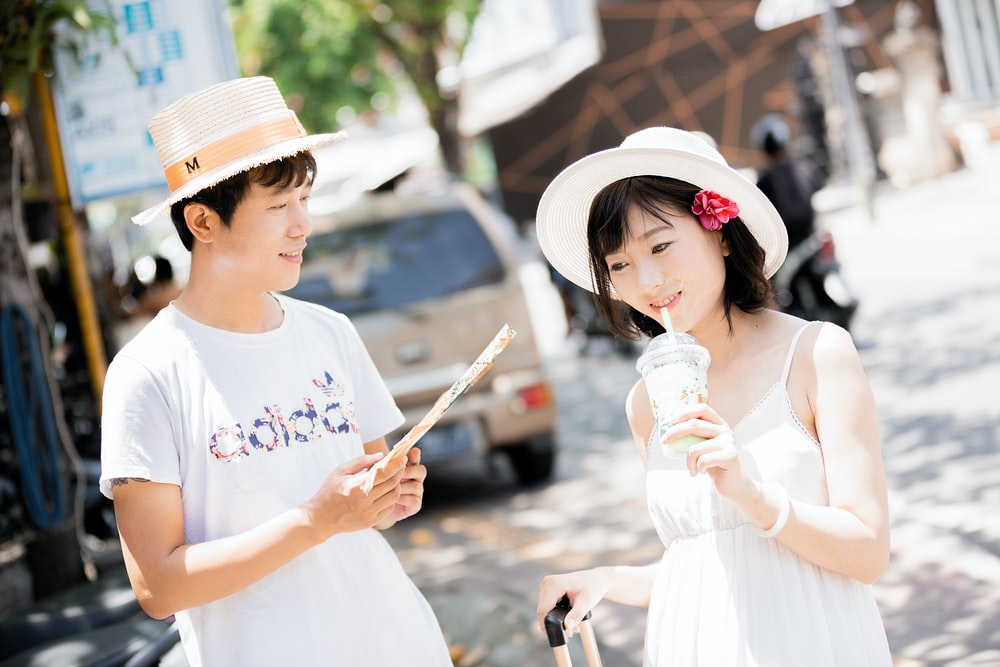 man and woman wearing hats holding disposable cups near vehicle during daytime