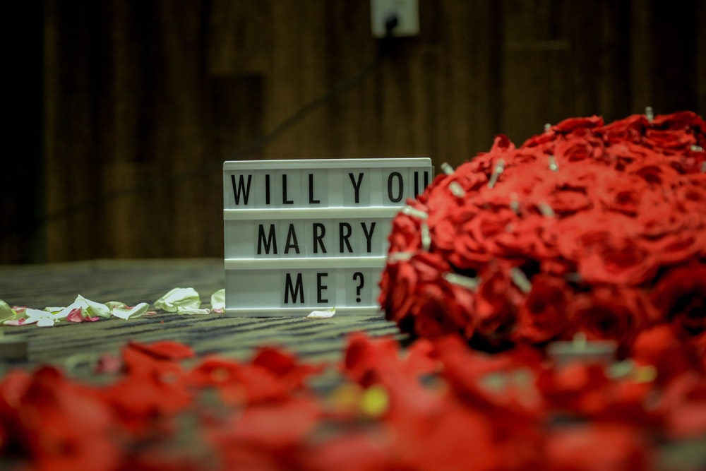 selective focus photography of Will you marry me board on brown surface