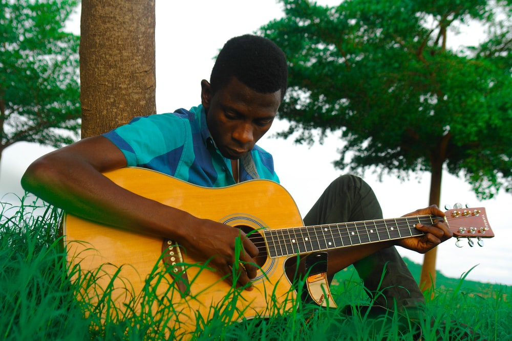man playing natural finish single-cutaway acoustic guitar while sitting on green grass near brown tree trunk during daytime