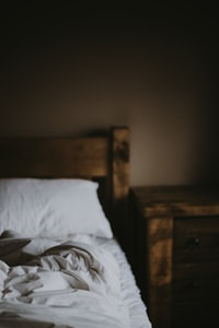 white cushion on bed near brown wooden nightstand