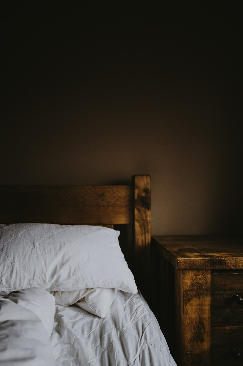 brown wooden bed frame and nightstand