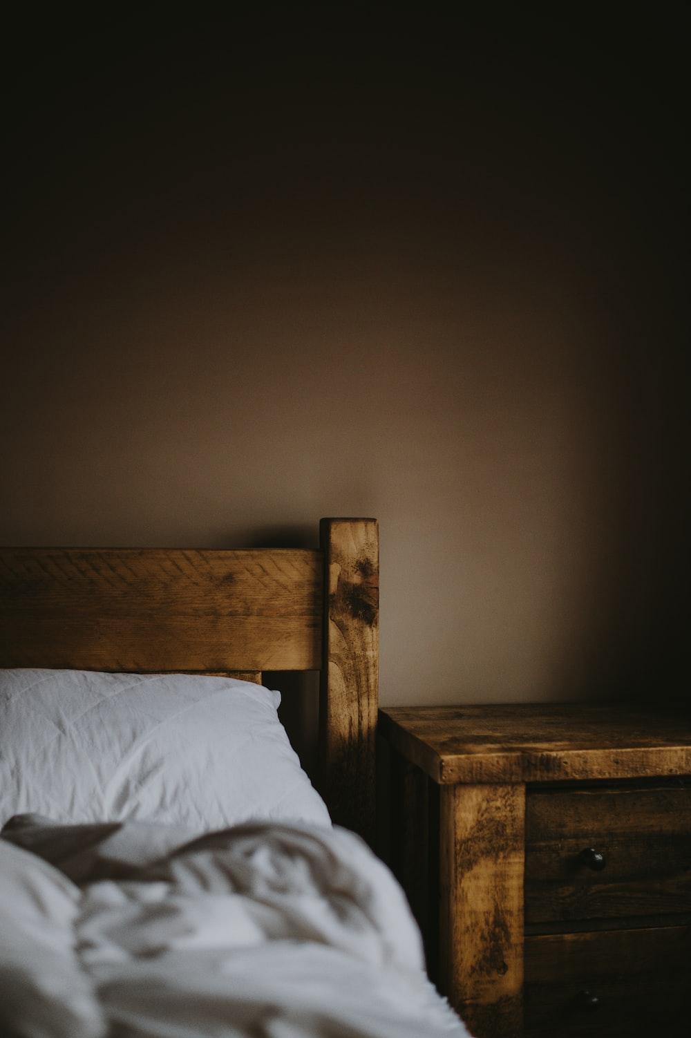 brown wooden nightstand beside bed