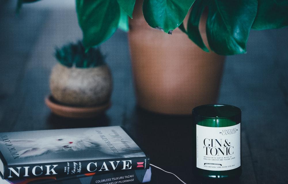 Nick Cave book beside Gun & Tonic tealight on black wooden table