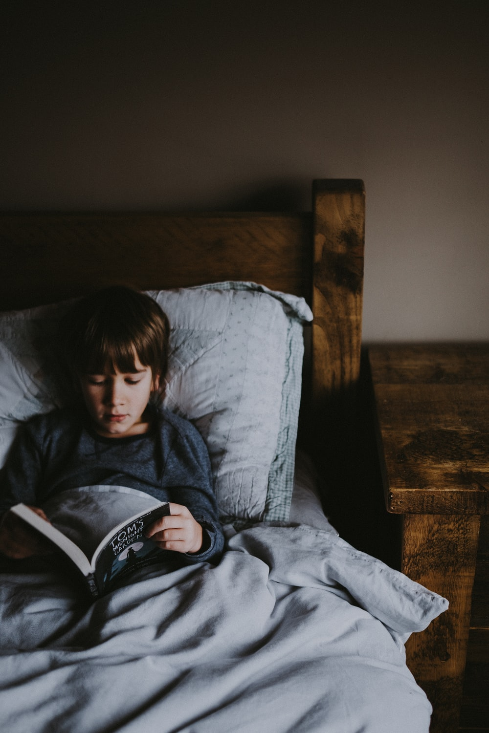 boy reading Tom's book on bed