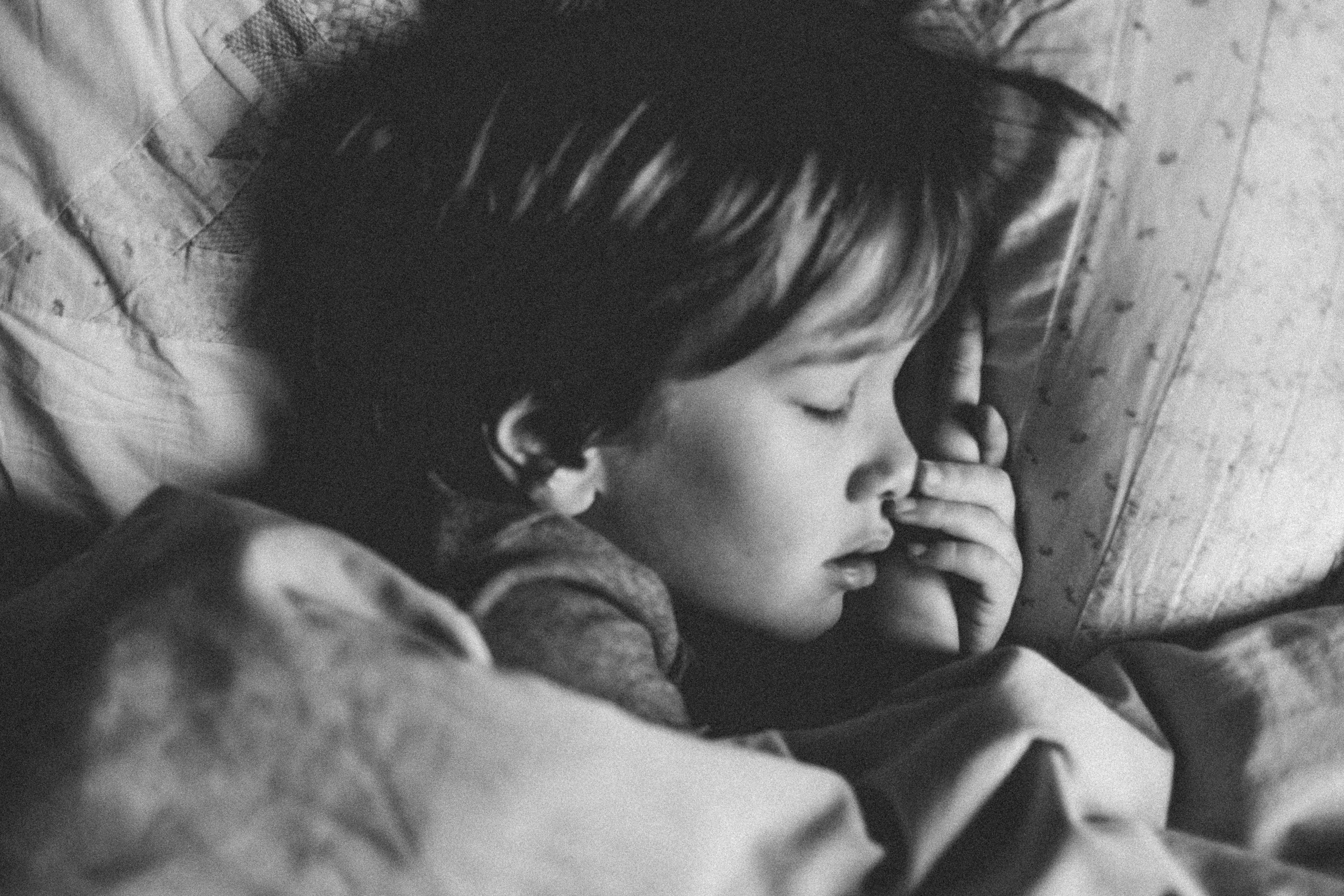 grayscale photo of girl sleeping on white pillow