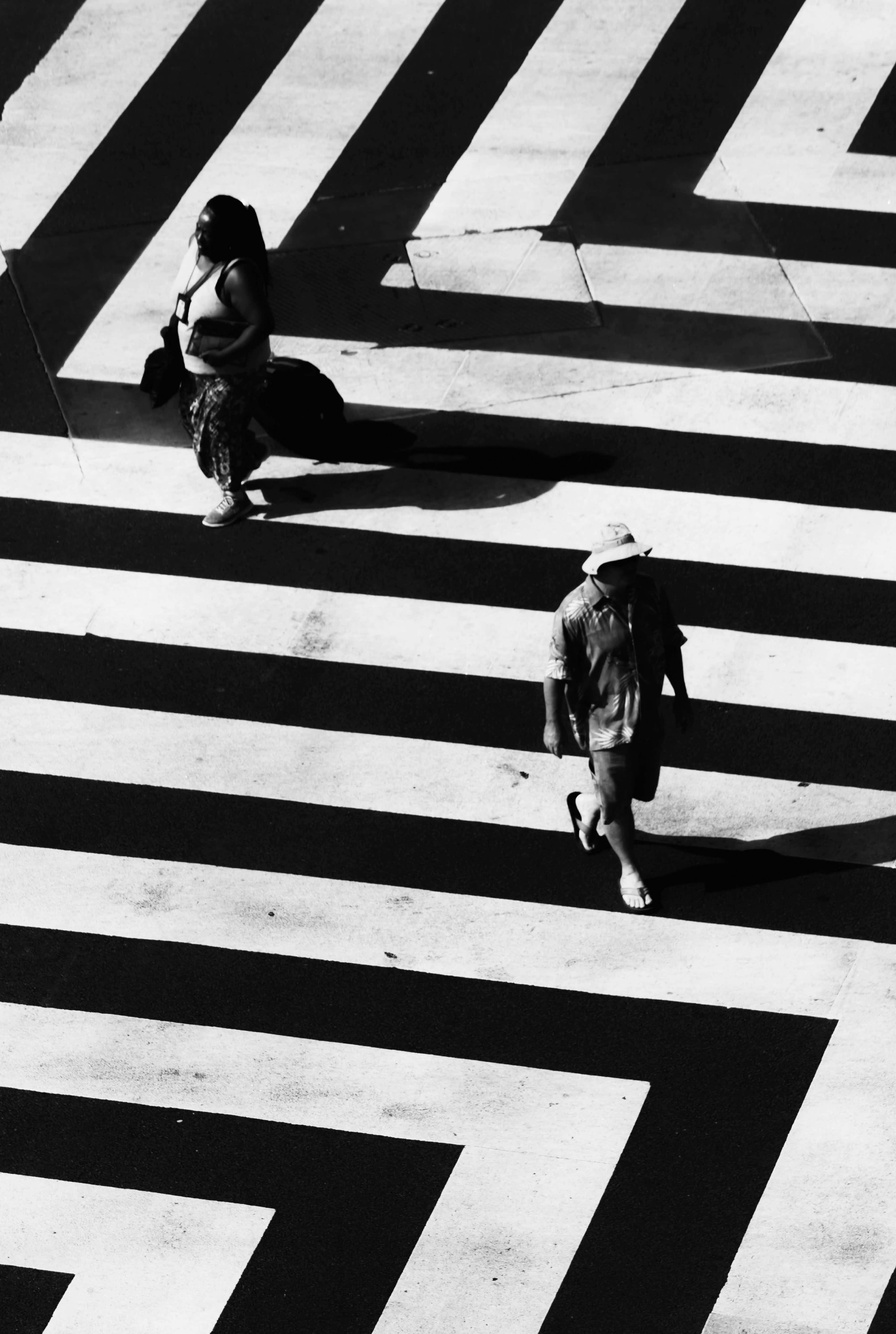 woman and man waling on white and black striped road