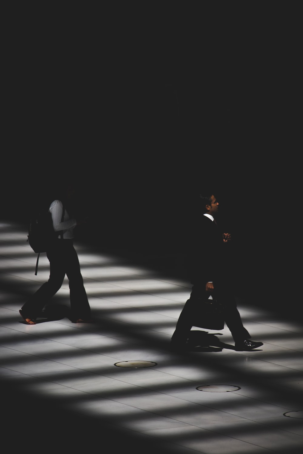 two person walking inside building with black lighting