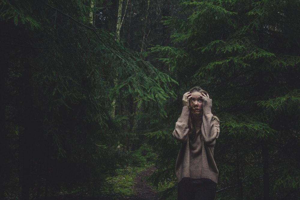 woman holding head standing between trees