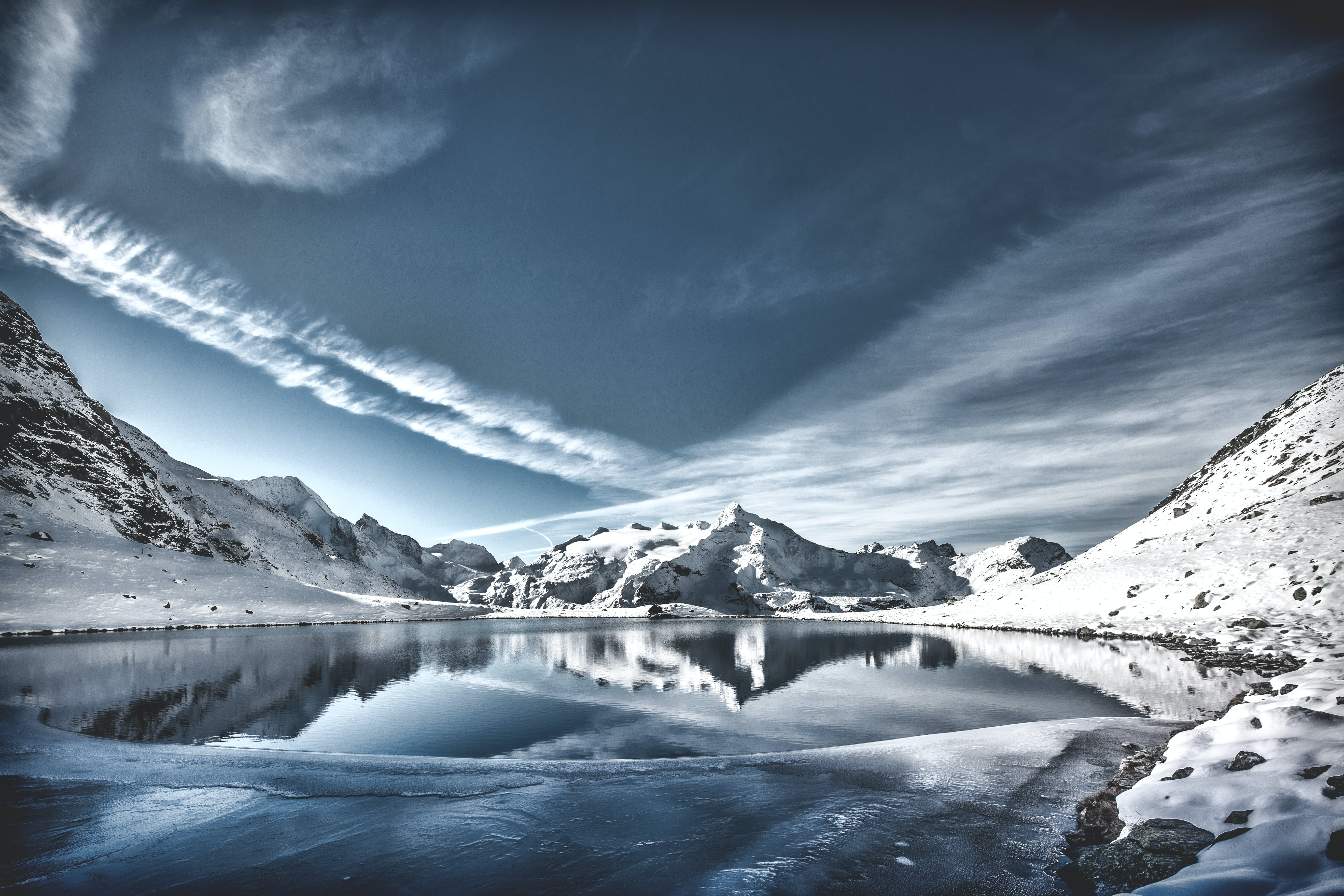 body of water between mountain range covered in snow under gray sky and white clouds at daytime