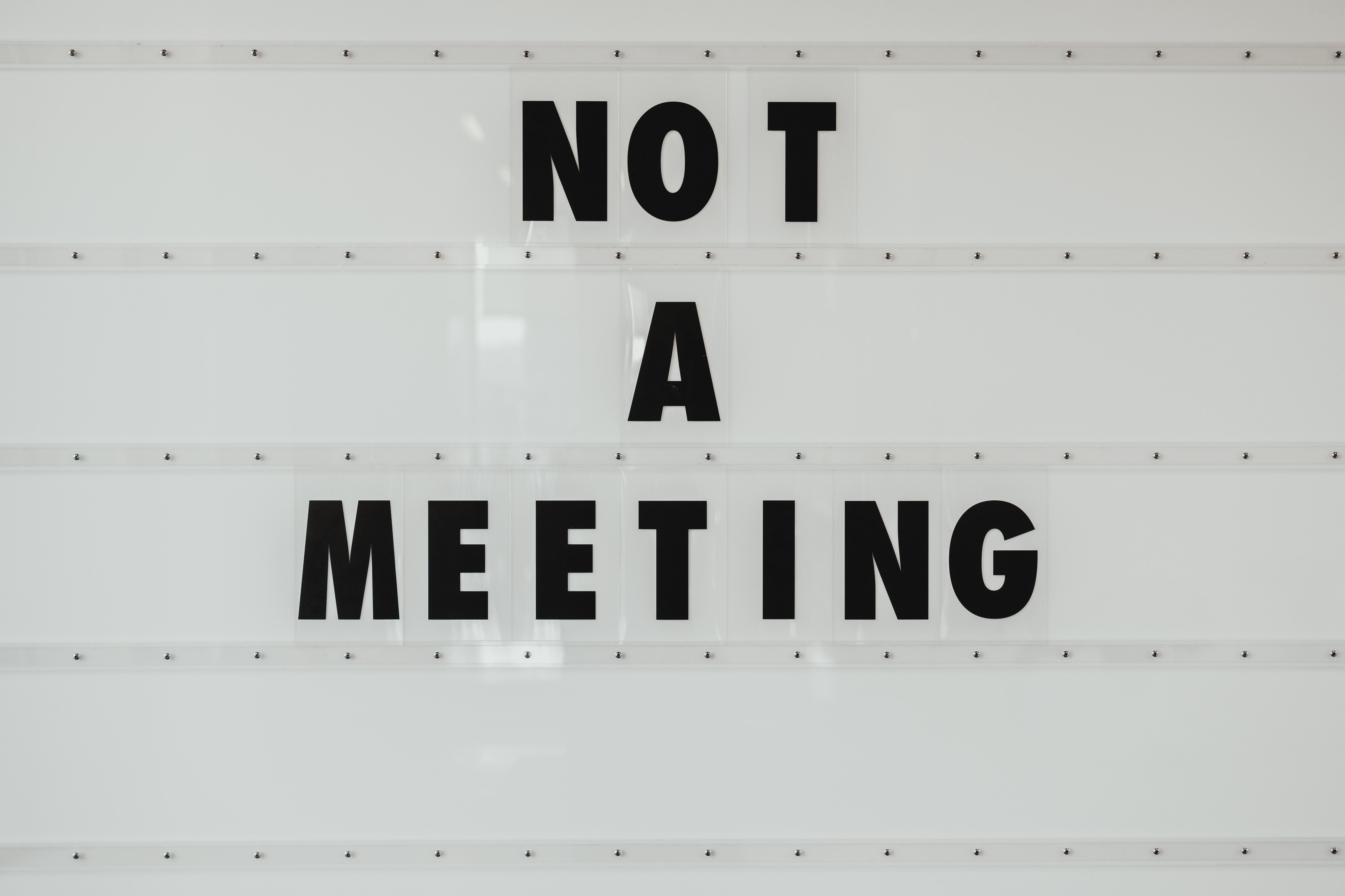 black note a meeting sign on wall