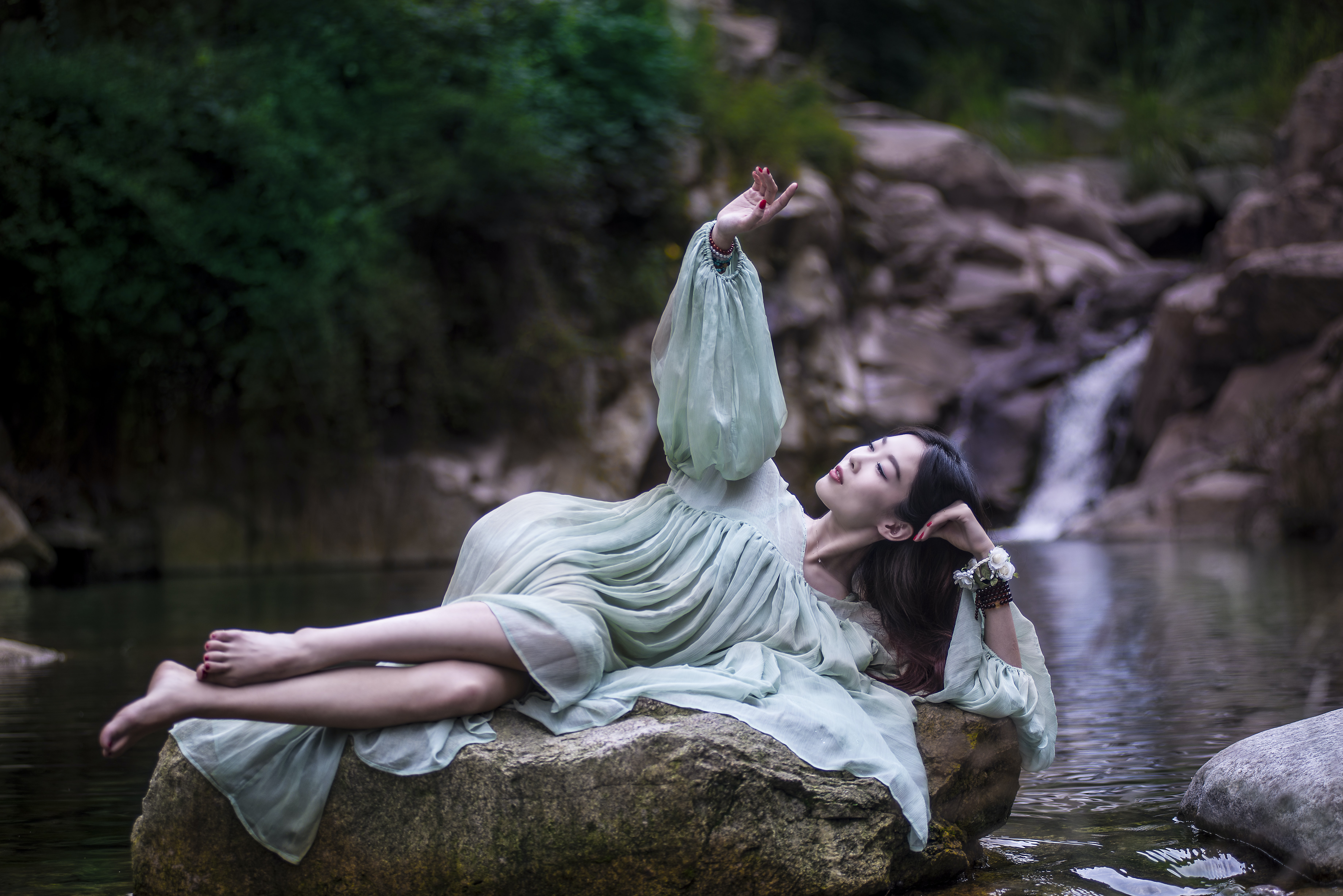 woman lying on large stone between flowing river