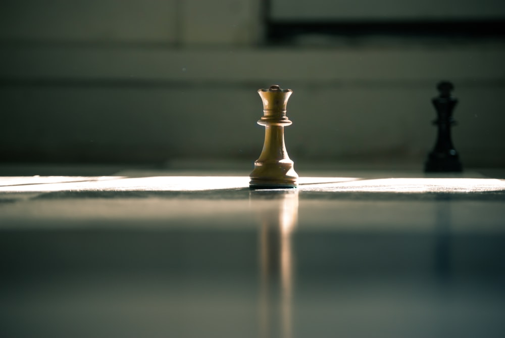 white queen chess piece on white surface