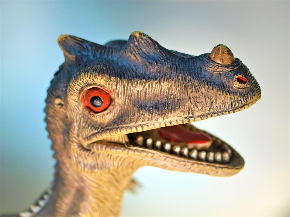 closed-up photo of gray dinosaur figurine
