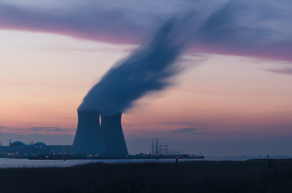 skyline photography of nuclear plant cooling tower blowing smokes under white and orange sky at daytime