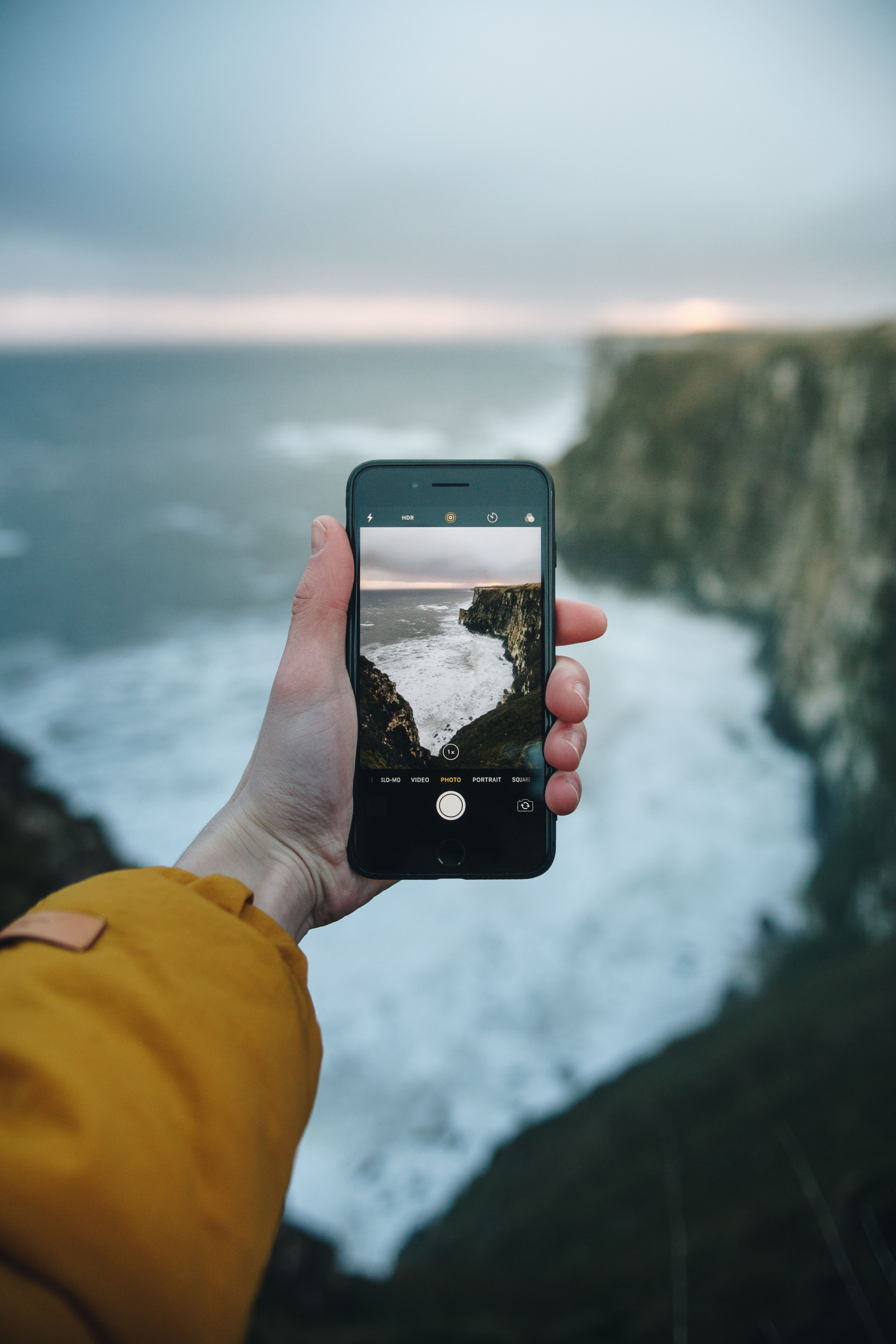 person holding phone taking picture of ocean wave