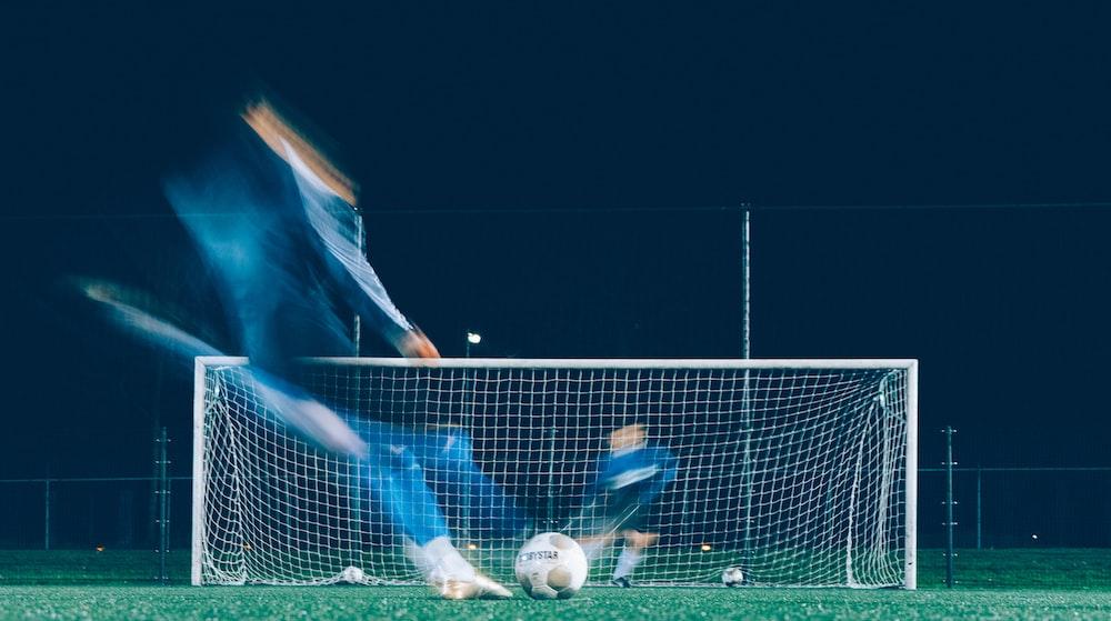 timelapse photo of soccer player kicking ball