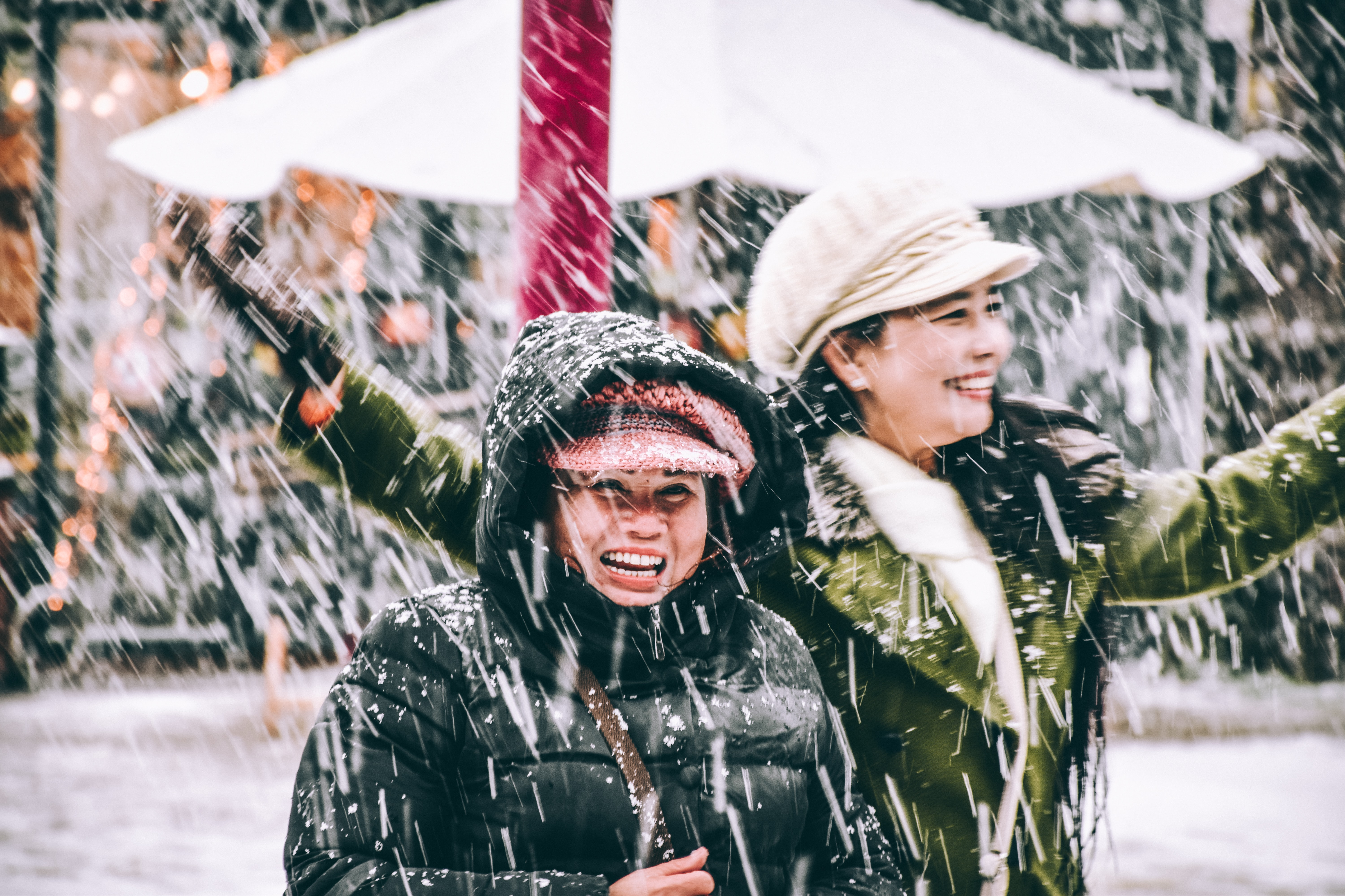 two women standing under snow storm