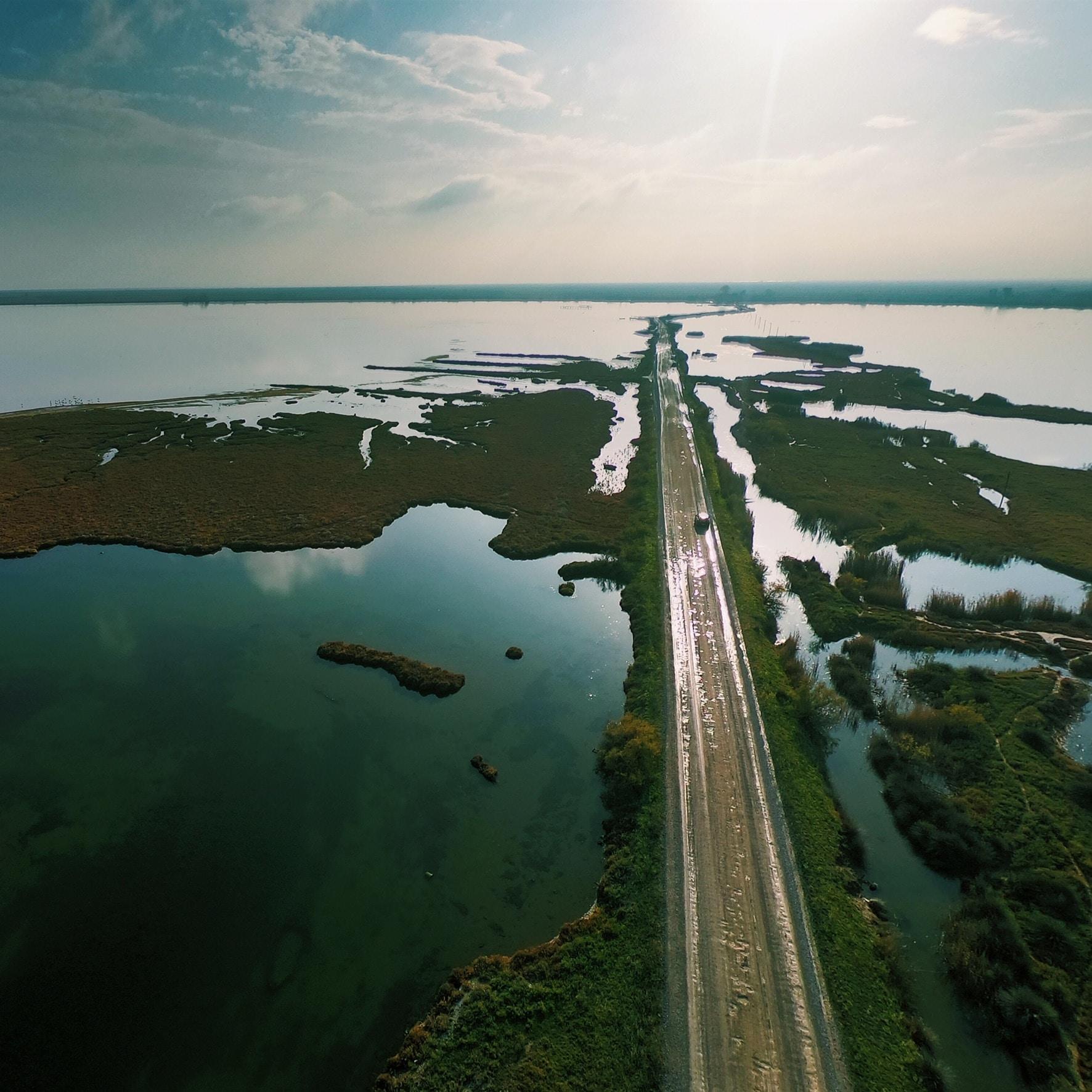 aerial photography of asphalt road in between body of water