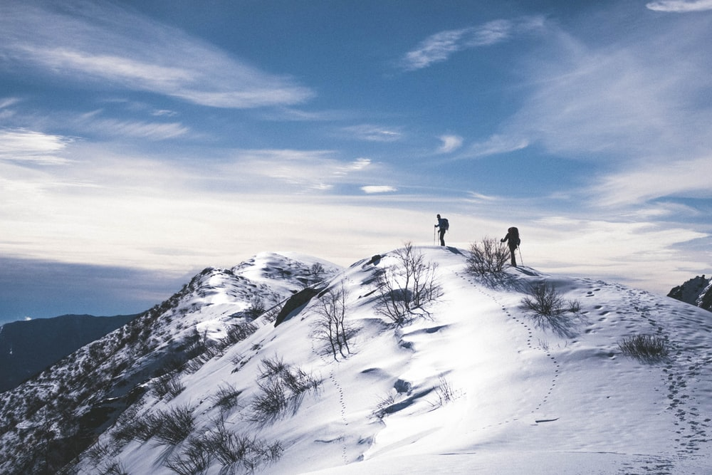 two person hiking on mountain with snow