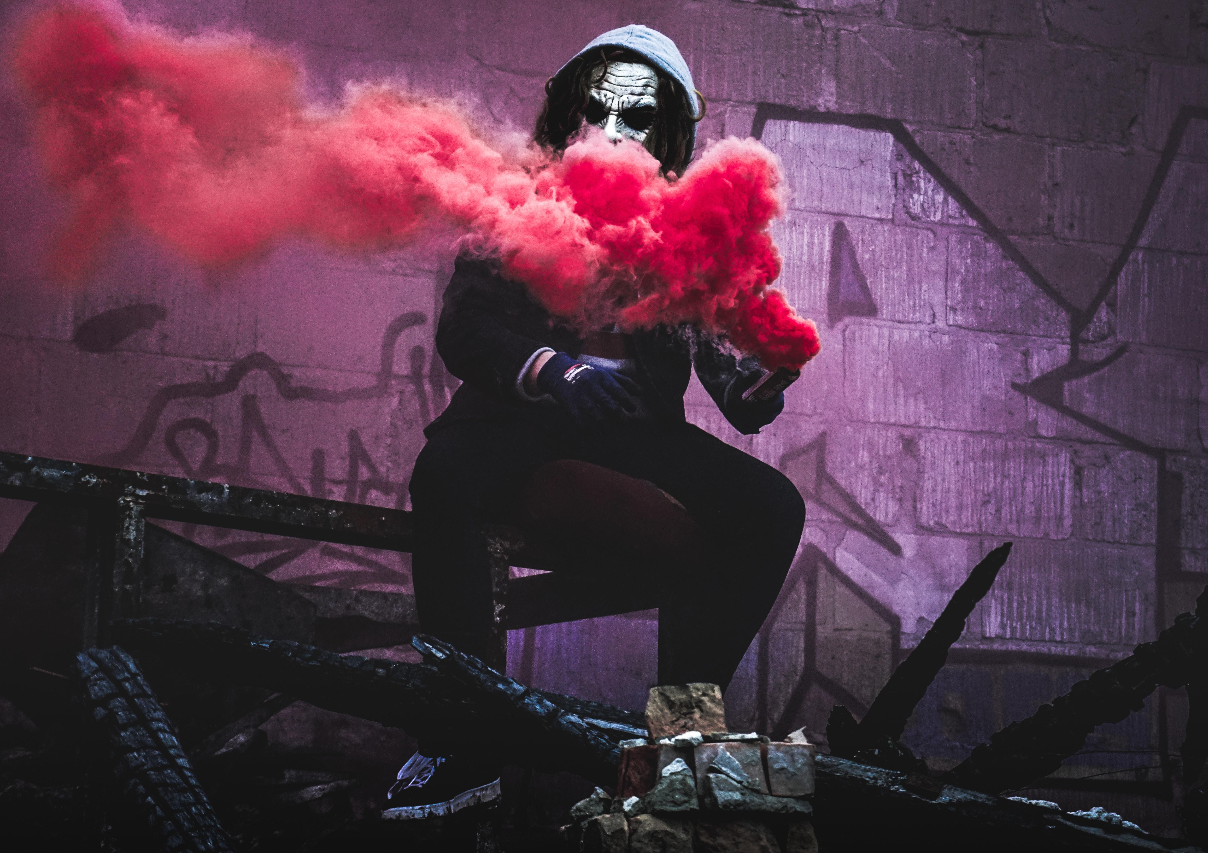 man sitting while holding red smoke signal